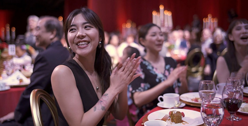 Woman smiles and applauds while sitting at banquet table