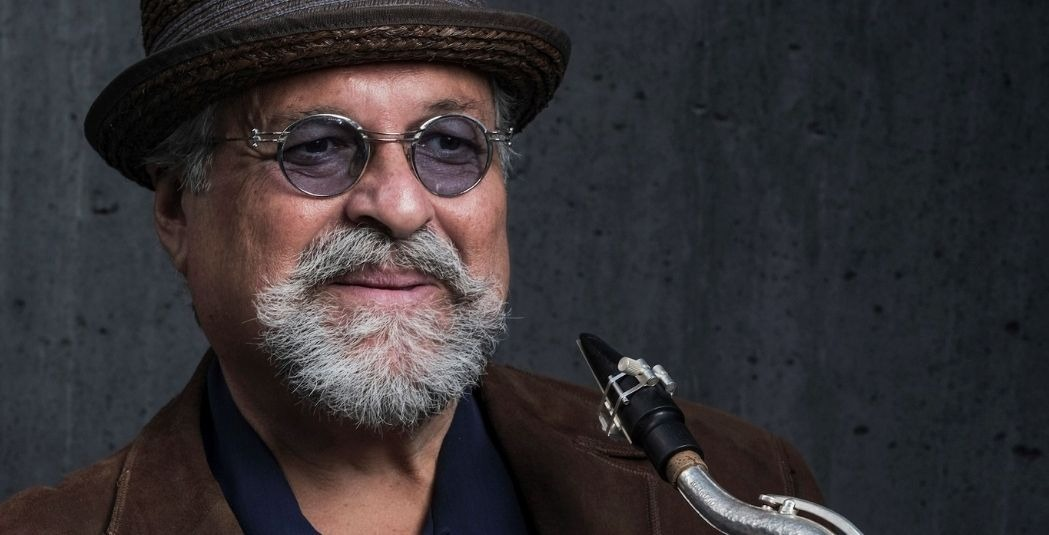 joe lovano wearing a hat and glasses and holding sax