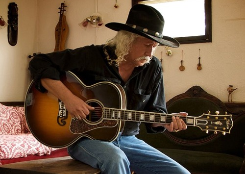 Arlo Guthrie playing the guitar