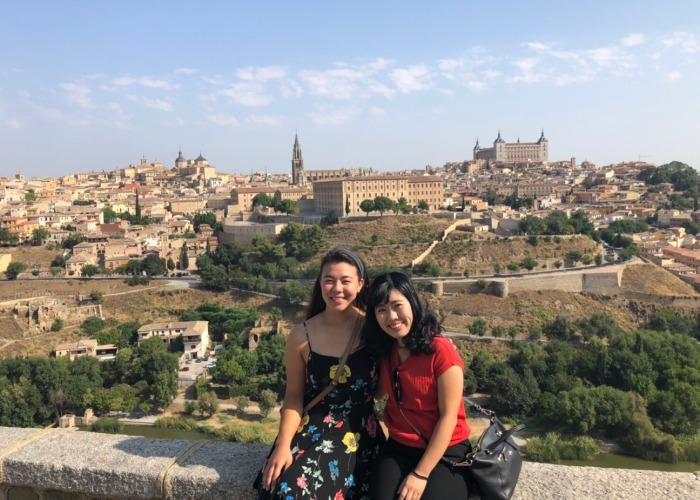 Two students in front of cityscape in Valencia, Spain