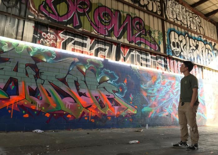 Student looking up at wall of graffiti