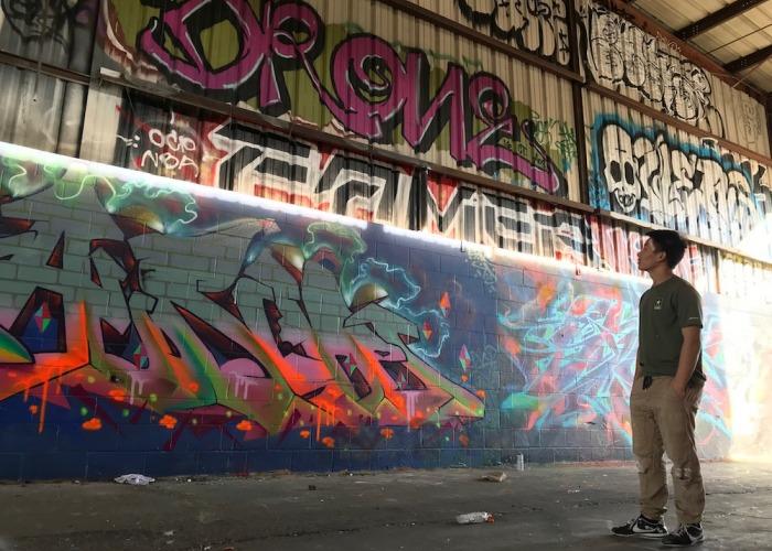 Soka University student looking up at wall of graffiti