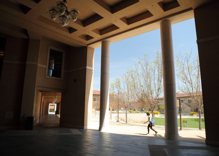 student walking under the exterior library columns