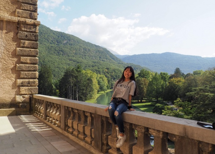 student sitting on ledge with green hills in background