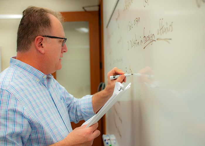 Peter Burns writes on a whiteboard