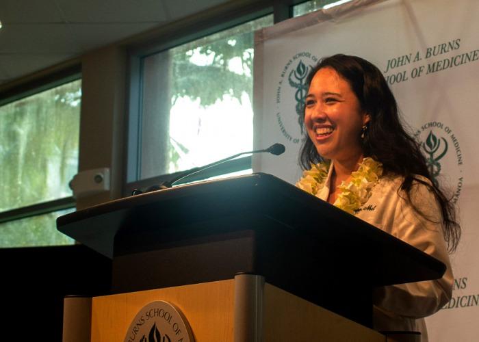 Erika Noel smiling behind a podium