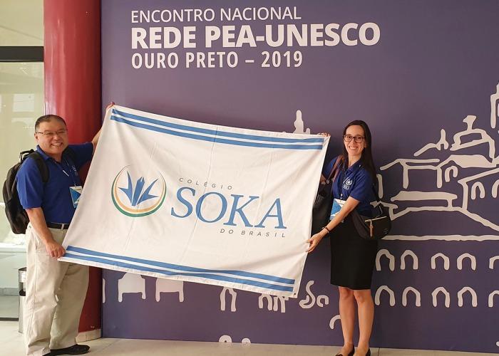 Two teachers holding Soka flag