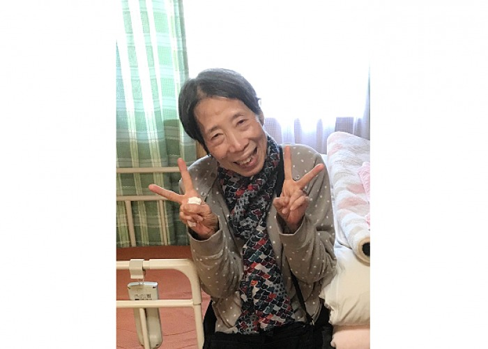 Mrs. Okabe flashing peace signs