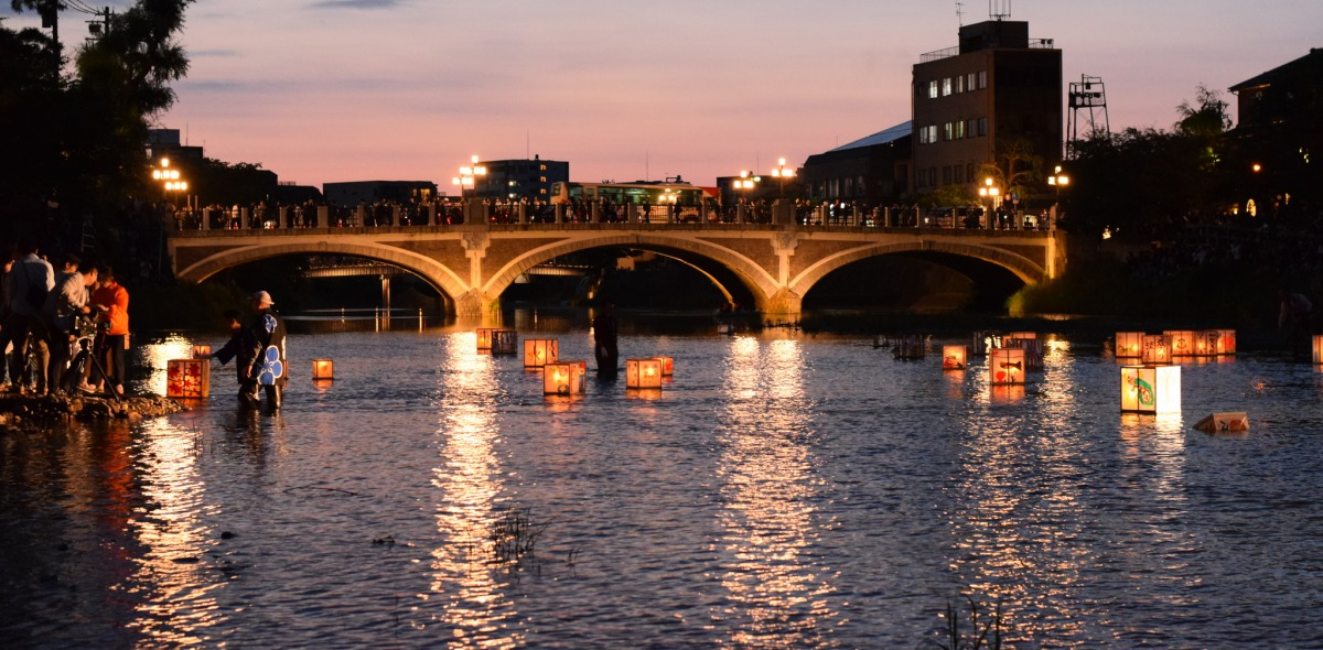 Picture of a bridge illuminated from behind by a sunset and underneath by lanterns floating on the water.