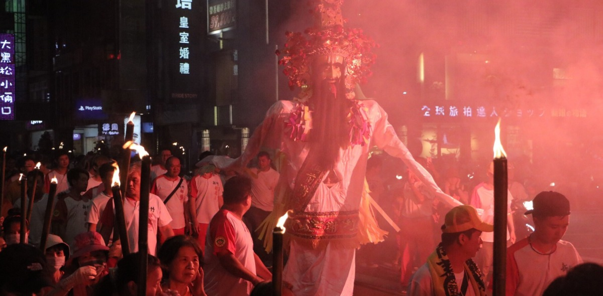 An effigy of a deity illuminated by red light is marched through the streets at night.