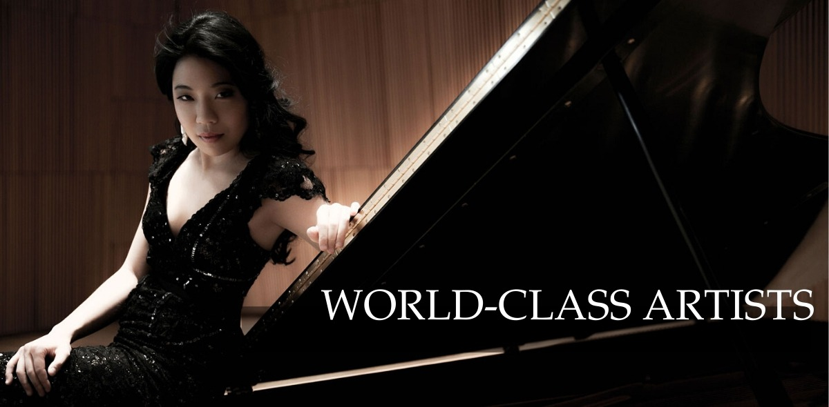 Joyce Yang wearing black dress leaning against a grand piano