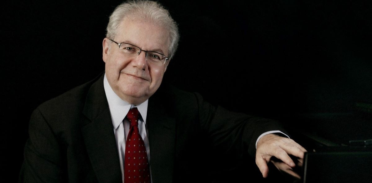 Emanuel Ax sitting at a piano wearing a suit and tie