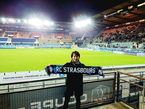 Student in front of football green with Strasbourg banner
