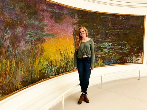 Student standing in front of large painting in France
