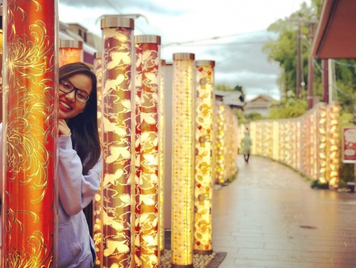Student smiling from behind light totems in Japan