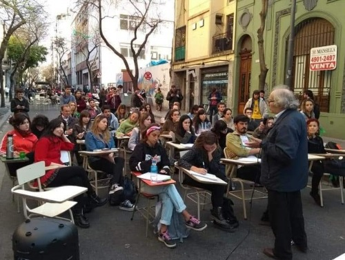 Students at tables on street in Buenos Aires