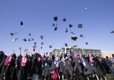 Image of students throwing graduation caps.