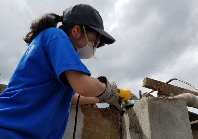 student working to rebuild house