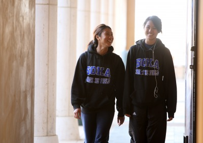 Two students walking wearing Soka sweatshirts