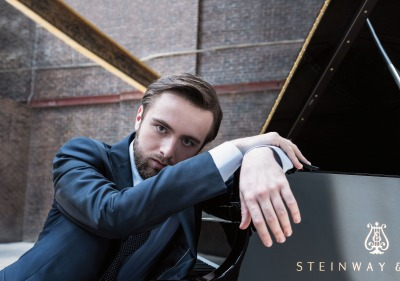 Daniil Trifonov sitting with hand on piano