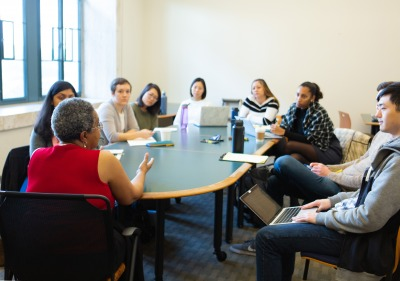 Image of students and a speaker sitting at a table.