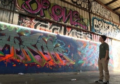 Soka University student looking up at wall of graffiti