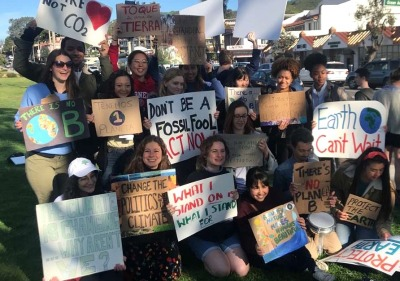 Students demonstrate with signs encouraging climate action