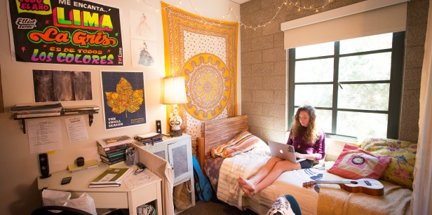 Girl sitting on bed in residence hall dorm room