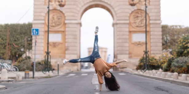 student doing cartwheel in front of arch