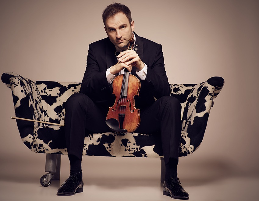 Stefan Milenkovish sitting on a couch with violin in hands.