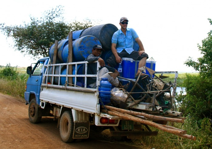 A picture of Michael Schaefer on a truck bed with multiple water barrels.