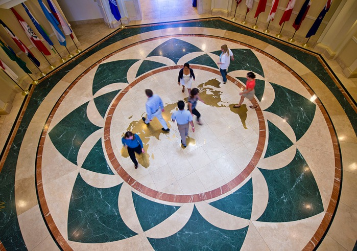 Students mingle on map of globe on the floor of Founders Hall