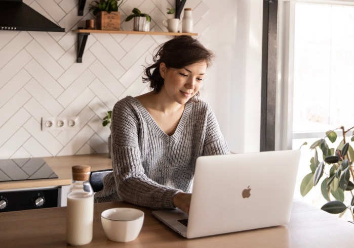 Girl Using Laptop in Kitchen