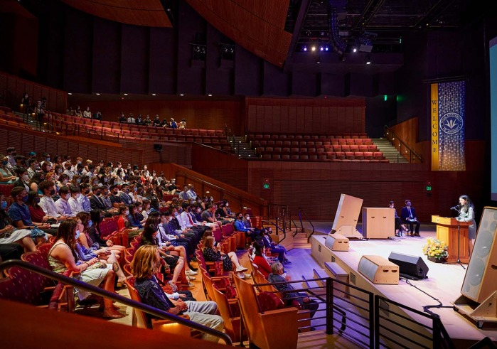 Person on concert hall stage speaks to students in audience