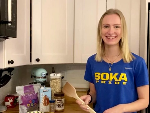 Blond woman wearing blue and yellow Soka T-shirt smiling in kitchen holding wooden spoon