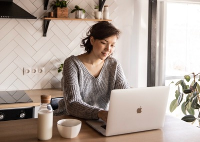 Girl Using Laptop in Kitchen