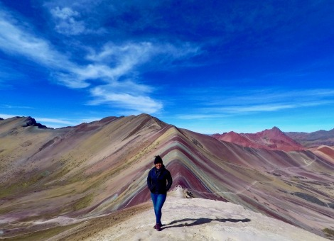 Delali standing in front of Spring Rainbow Mountain in Ecuador