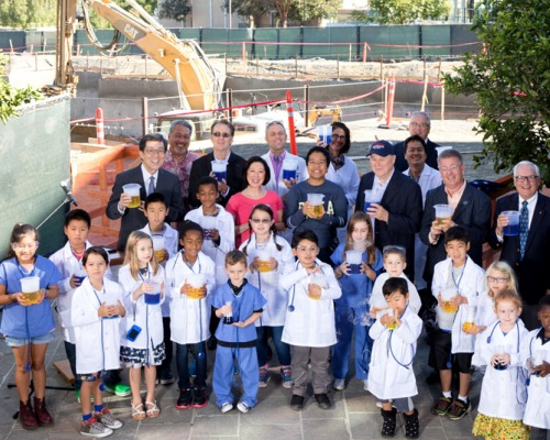 Group shot of dignitaries and young children dressed in medical and lab coats